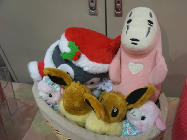 A pink Ghibli character sits among other cute plushies