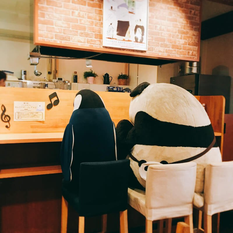 The Shirokuma Cafe penguin and panda sitting at a table
