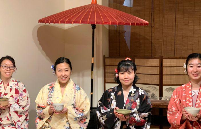 Four people enjoying Kyoto tea ceremony with sweets while in kimono in one of the best Kyoto food tours