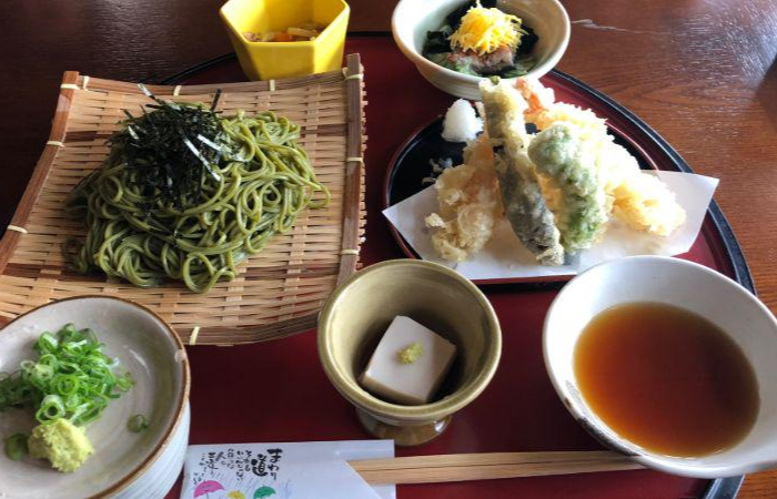 A table of food, including matcha soba noodles, fried tempura, soft, dipping sauce, and a side of dishes, served in one of the best Kyoto food tours