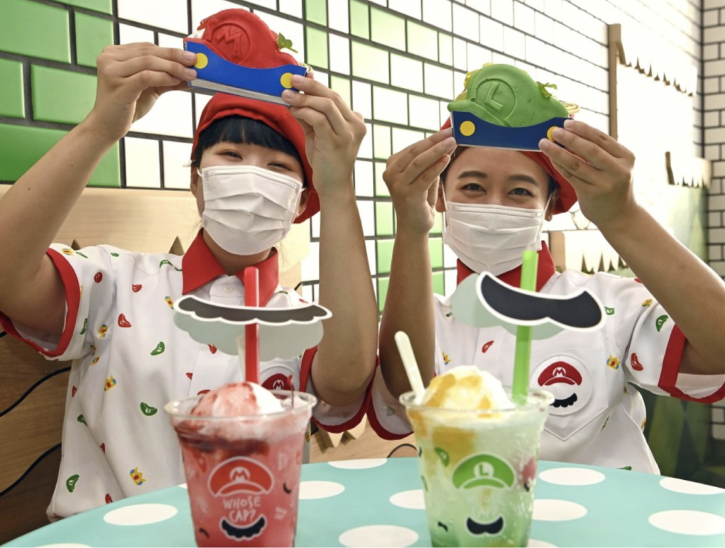 Two staff holding up Mario sweets and drinks