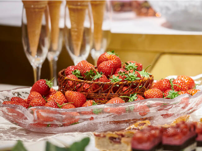 A pile of strawberries with wine in the background