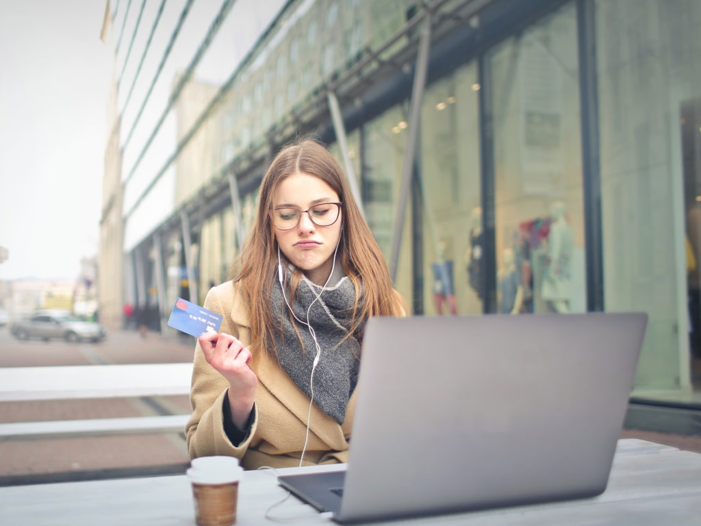 Woman sitting at a table with her laptop, looking disappointed at her credit card
