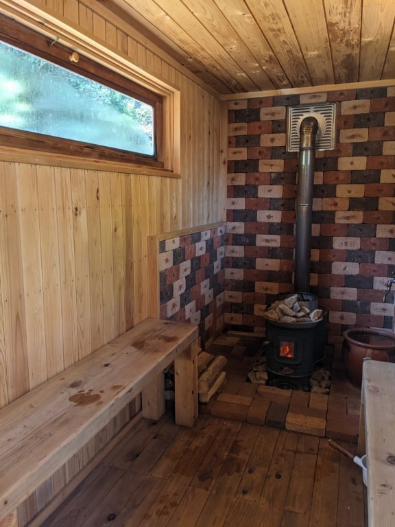 The inside of the sauna shows a wooden bench, brick wall, and a black wood-burning stove with stones and herbs resting on top.