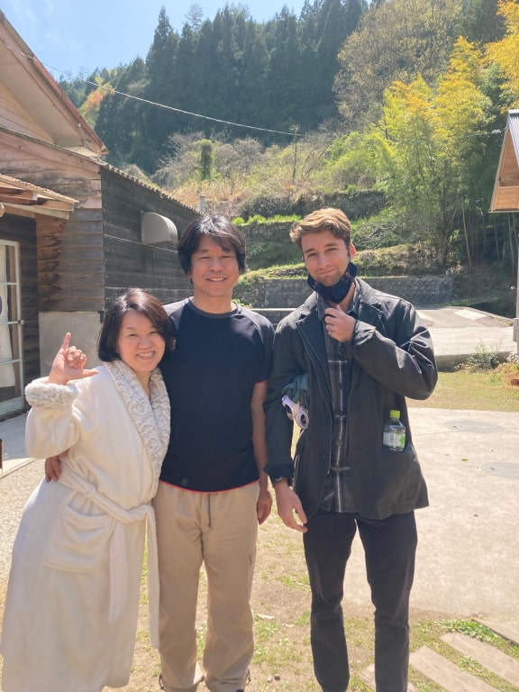 Two men and a woman who left Tokyo in a robe pose outside.