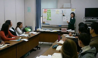 A Japanese instructor teachers with a whiteboard and textbook at the front of the classroom, while adult students at their desks.