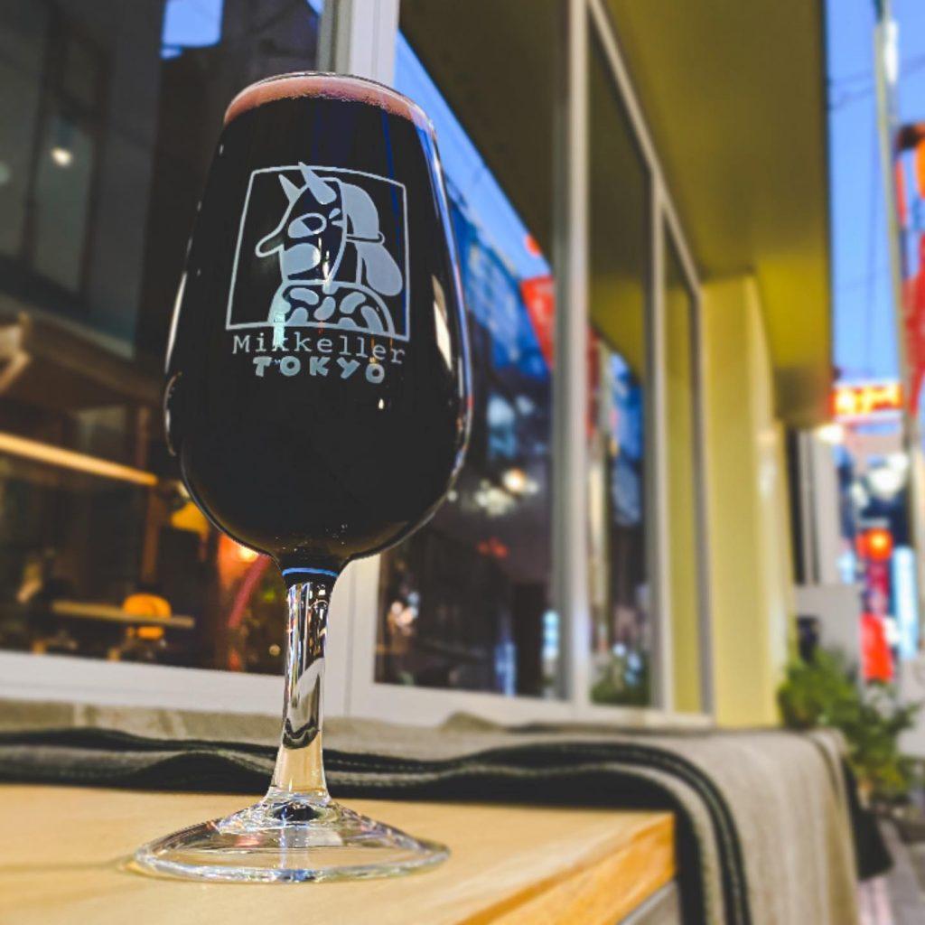 A glass with the Mikkeller Tokyo logo full of wine, shot outside the Mikkeller bar.