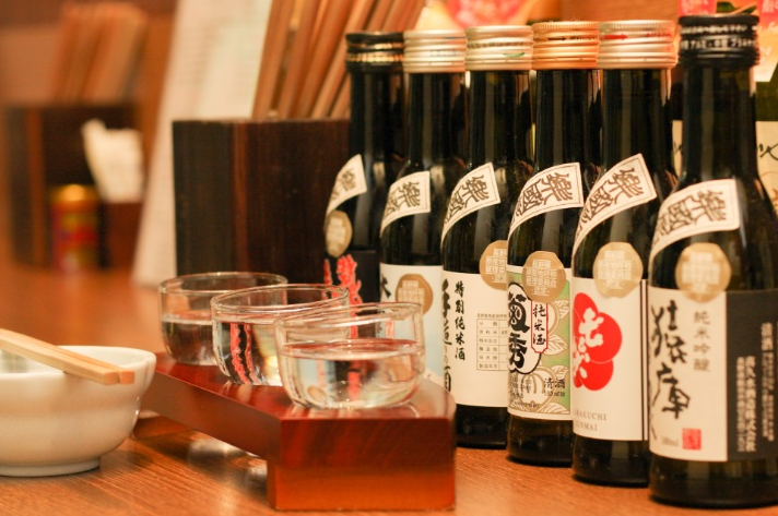 A photo of different sake bottles and glasses filled with sake.