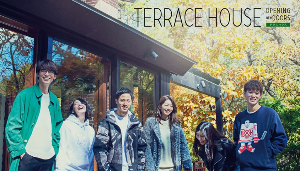 """Six Japanese people stand outside a house and a trees with fall colors, the title """"Terrace House: Opening New Doors"""" written above them."""