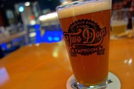 A glass with Two Dog's logo, filled with beer on a table.