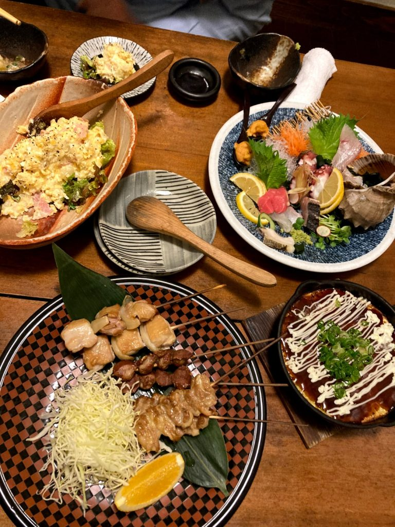 Potato salad, grilled chicken, sashimi, and other Japanese foods on dishes.