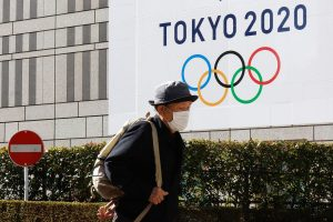 An old man in front of a Tokyo 2020 Olympics banner