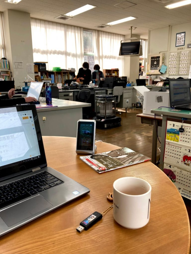 A computer and mug of coffee sit in the foreground on a desk, with people in a staffroom in the background.