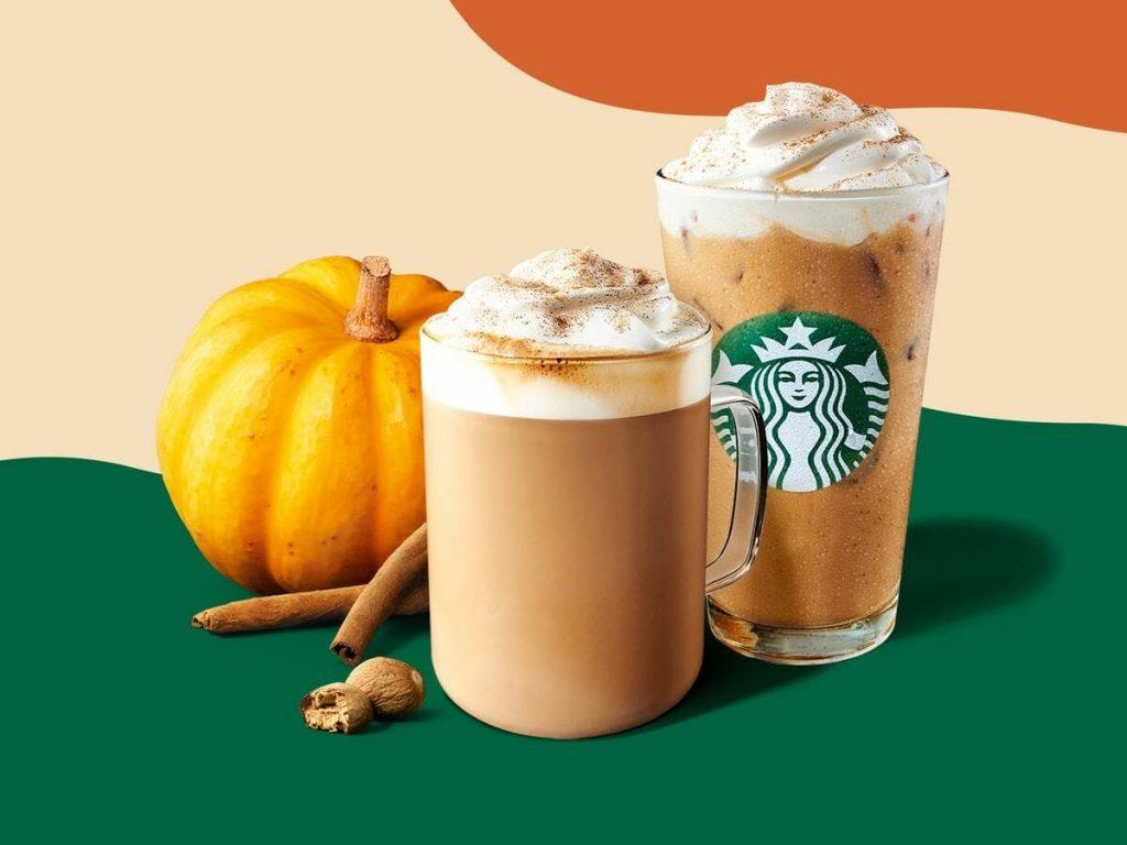 Pumpkin spice latte next to a pumpkin and cinnamon sticks
